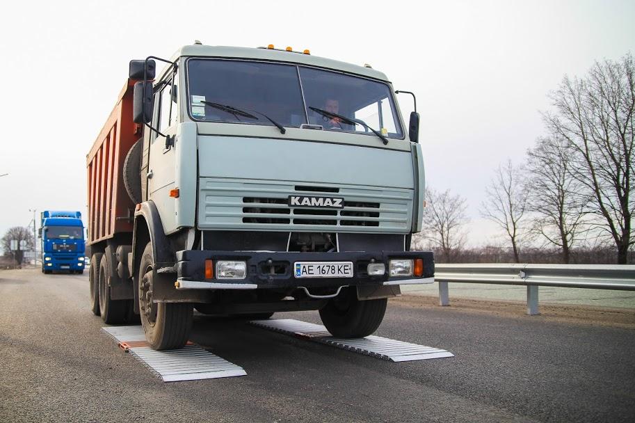 Вантажівка проїжджає по двох паралельних платформах електронних ваг